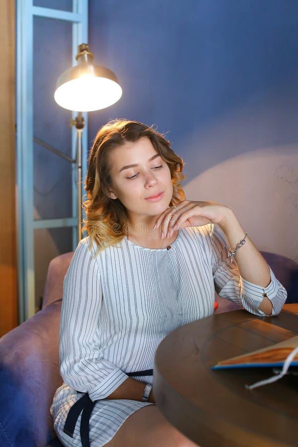 La donna abbastanza femminile dei giovani distoglie lo sguardo con gli occhi e lo smil del crollo fotografia stock libera da diritti