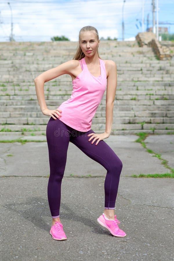 La donna abbastanza giovane di misura che fa l'allungamento si esercita in parco fotografia stock