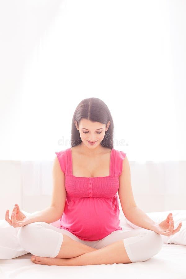 La donna abbastanza incinta sta meditando a casa fotografia stock libera da diritti
