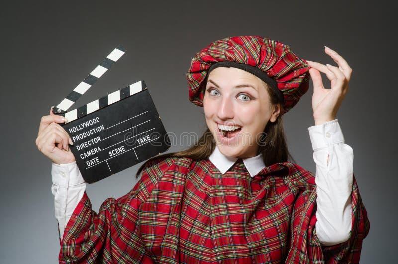 La donna in abbigliamento scozzese nel concetto di film fotografie stock