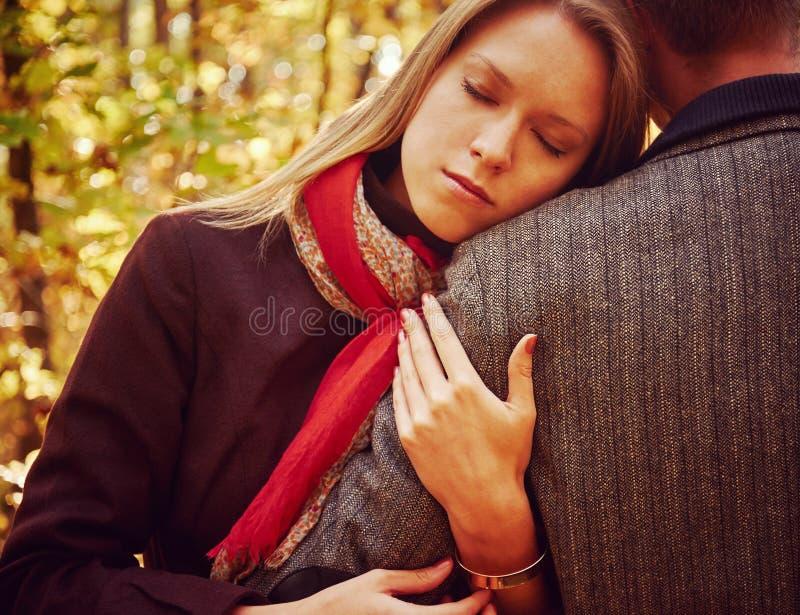 La donna abbraccia un uomo nel parco di autunno immagini stock libere da diritti