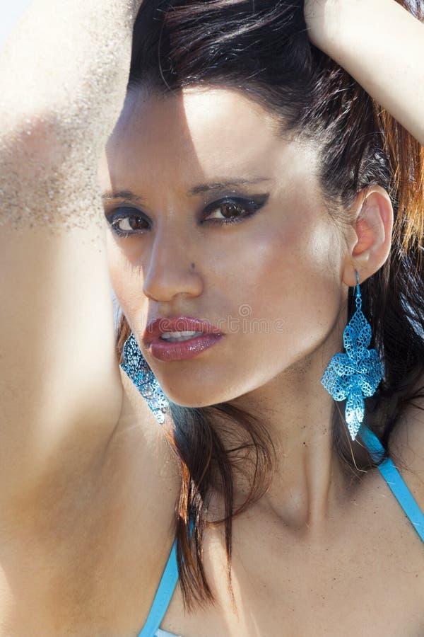 La donna abbronzata sensuale della spiaggia con lo sguardo intenso osserva immagini stock libere da diritti