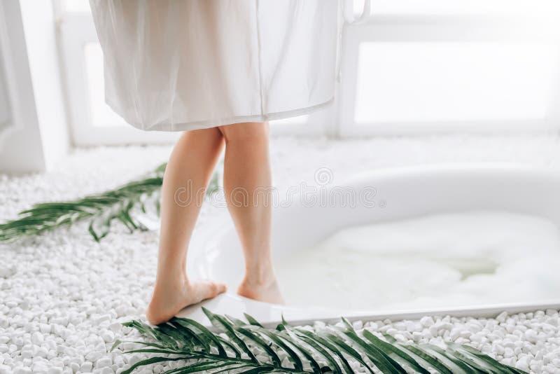 La donna in accappatoio bianco immerge le gambe nel bagno fotografie stock libere da diritti