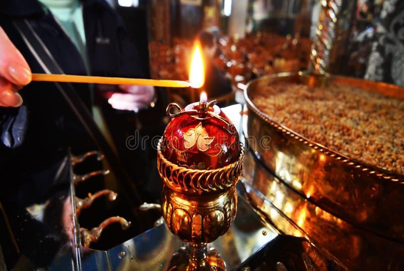 La donna accende la candela dentro la chiesa fotografie stock libere da diritti