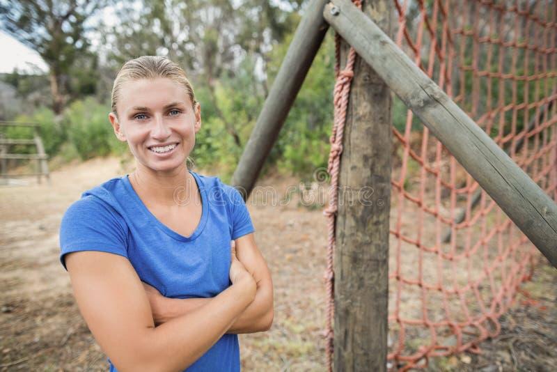 La donna adatta che sta con le armi ha attraversato durante l'addestramento di campo di addestramento immagini stock