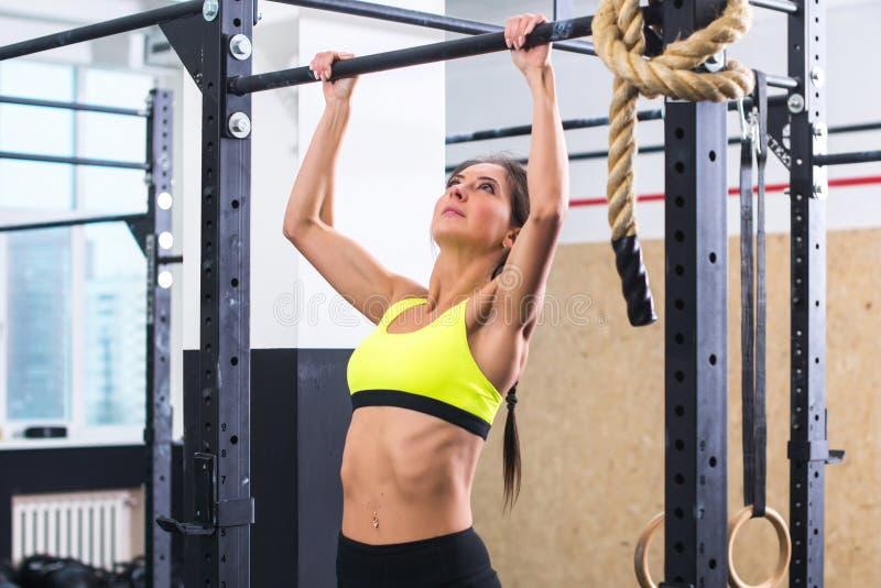 La donna adatta dell'atleta che esegue la tirata aumenta in una barra che si esercita alla palestra immagini stock libere da diritti