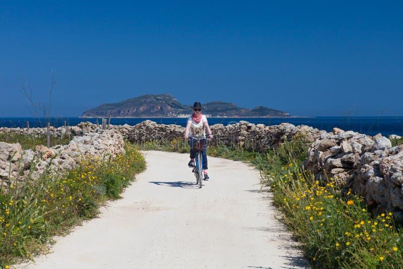 La donna adulta è ciclismo all'isola di Favignana, Italia immagini stock