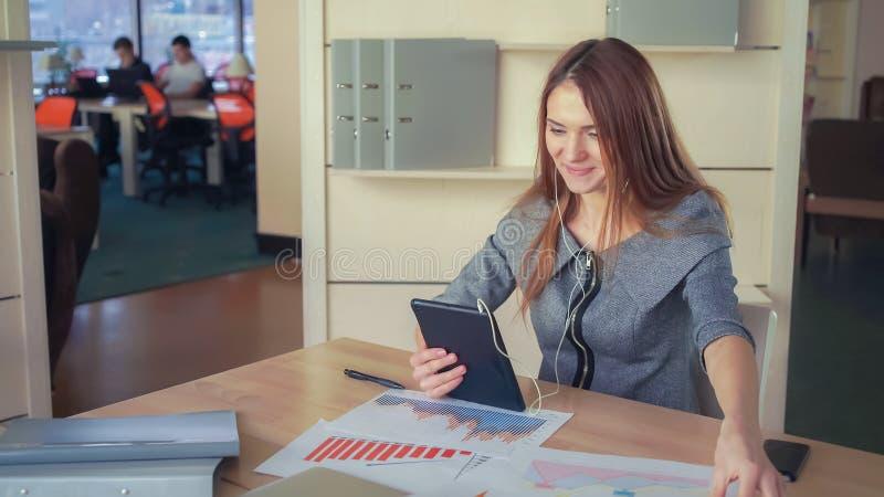 La donna adulta che parla con il cliente sulla compressa immagine stock