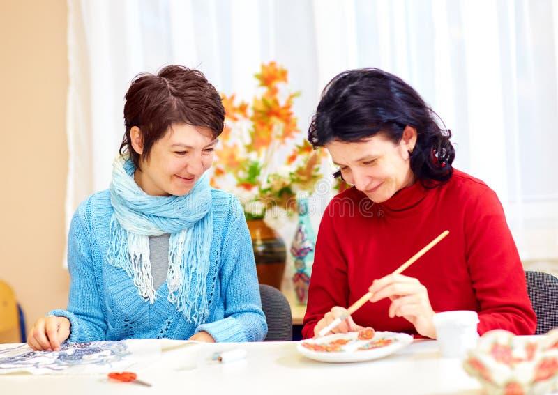 La donna adulta con i bisogni speciali è impegnata dentro handcraft nel centro di riabilitazione fotografia stock
