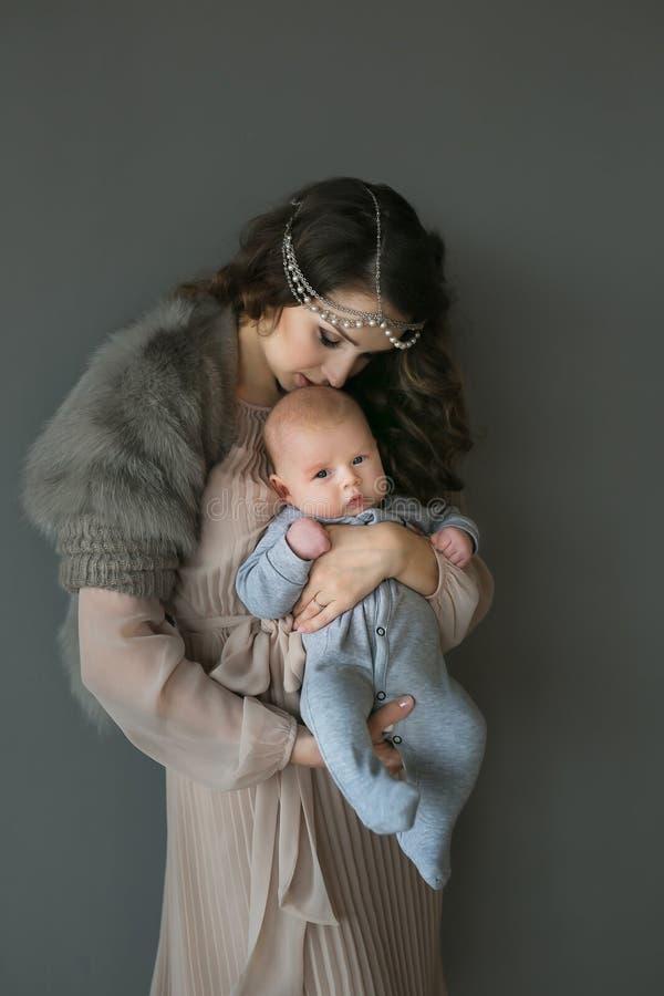 La donna adulta giovane tiene su un infante delle mani e lo bacia fotografia stock