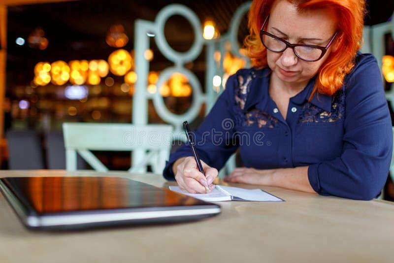 La donna adulta si siede in un caffè accanto ad un computer portatile e registra qualcosa in un taccuino fotografia stock