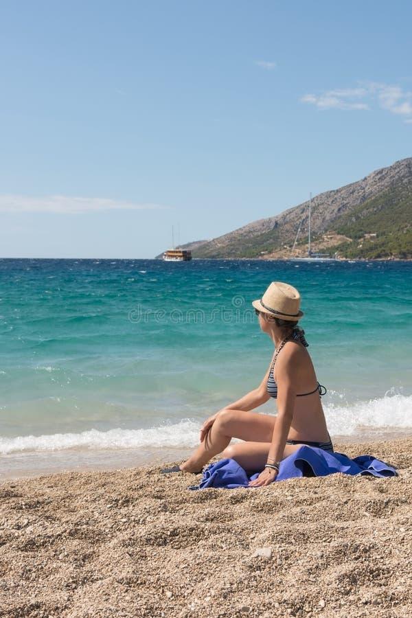 La donna adulta in un costume da bagno vede il mare sulla spiaggia fotografia stock libera da diritti