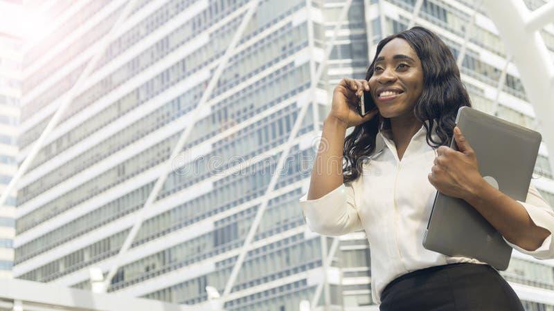 La donna africana di affari del ritratto utilizza il telefono cellulare astuto fotografia stock libera da diritti
