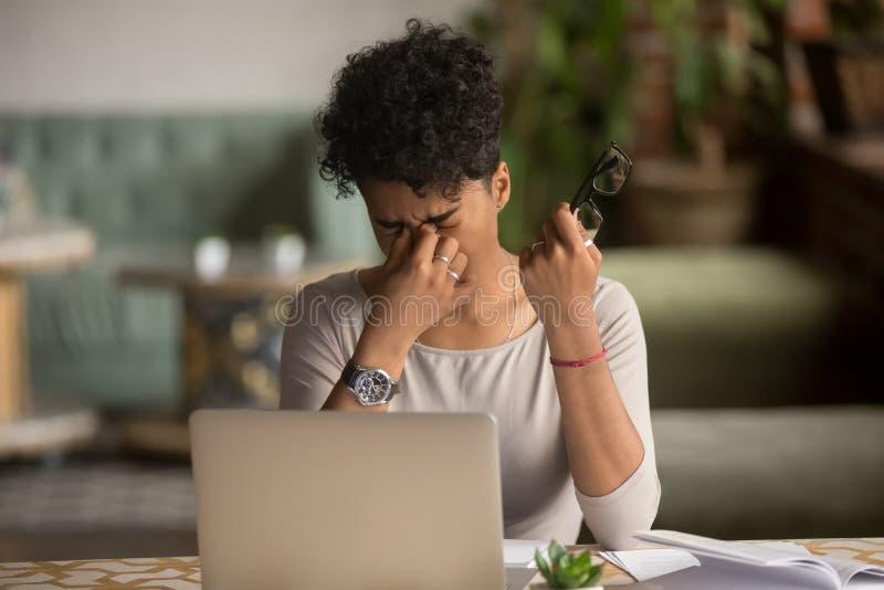 La donna africana stanca sovraccarica che tiene i vetri ritiene l'astenopia immagine stock libera da diritti