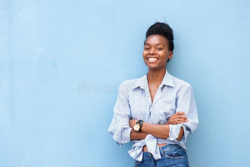 La donna afroamericana che sorride con le armi ha attraversato su fondo blu fotografia stock