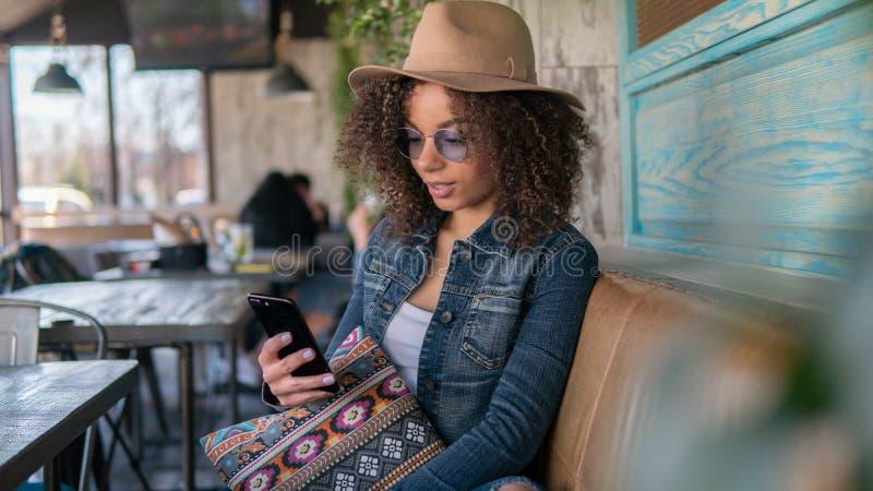 La donna afroamericana chiacchiera il caffè online e dell'interno fotografia stock