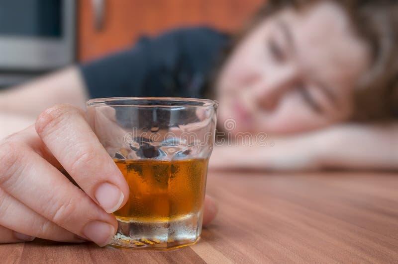La donna alcolica sta dormendo sulla tavola Vetro con alcool a disposizione fotografia stock libera da diritti