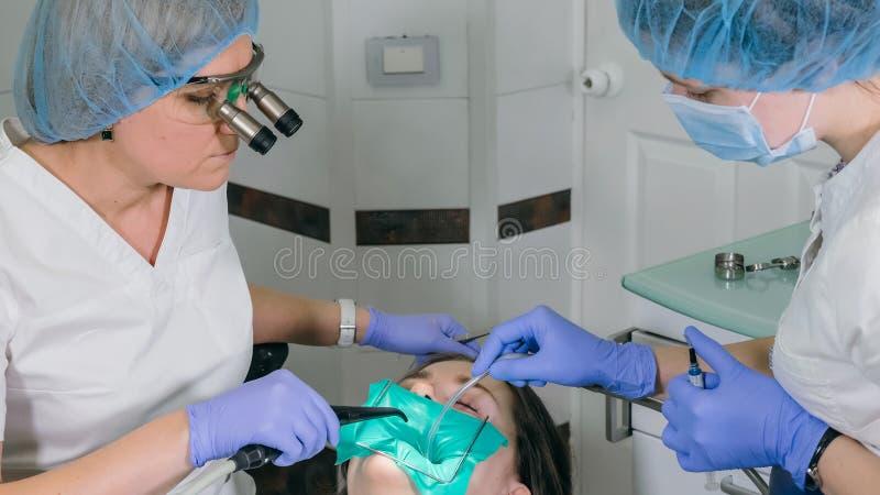 La donna alla clinica del dentista convince il trattamento dentario per riempire una cavità in un dente Ripristino dentario e mat immagine stock