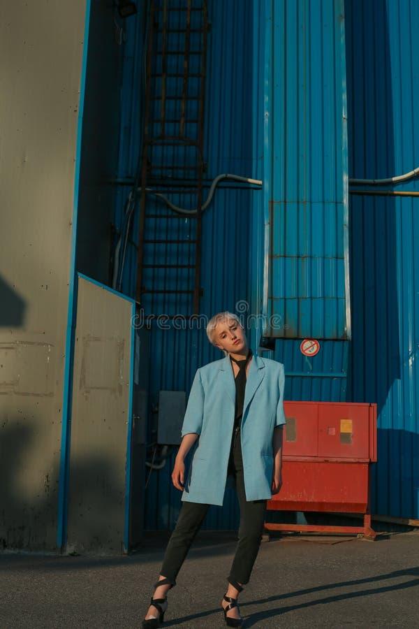 La donna alla moda sta posando vicino alla parete luminosa del metallo fotografia stock