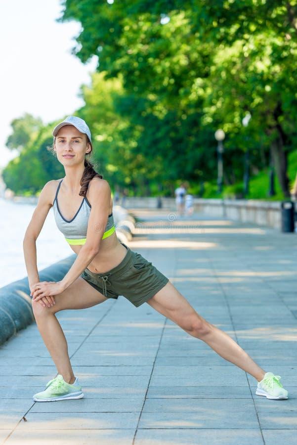 la donna allegra in abiti sportivi con una figura muscolare sta scaldandosi sull'argine della città fotografia stock libera da diritti