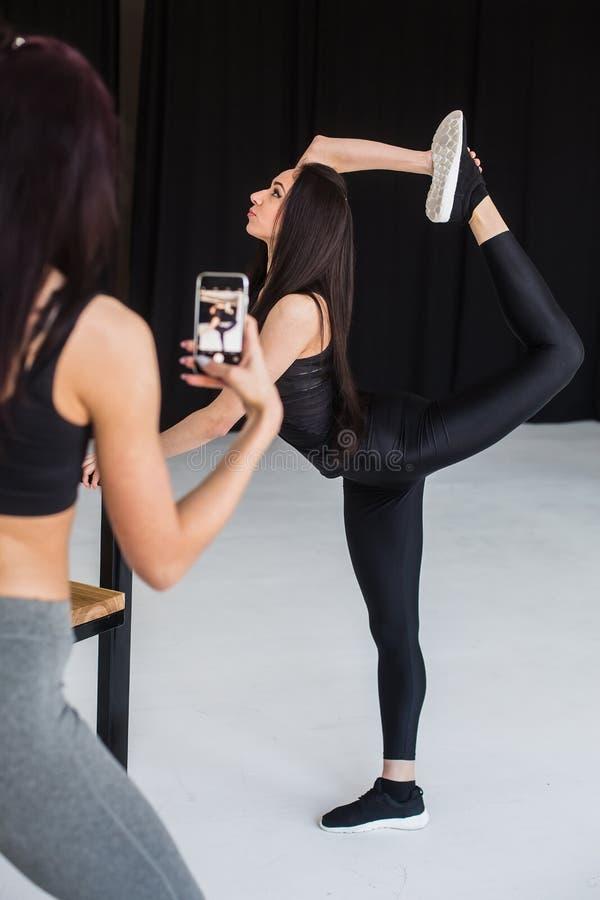 La donna allegra attraente di forma fisica sta facendo la posa di yoga dell'arco stante mentre il suo amico castana sta prendendo immagini stock