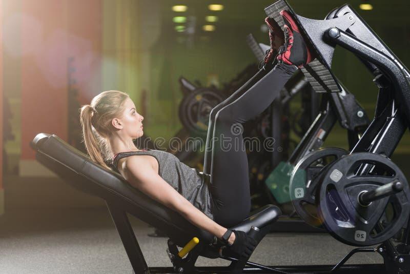 La donna allegra che usando i pesi preme la macchina per le gambe Ginnastica fotografia stock libera da diritti