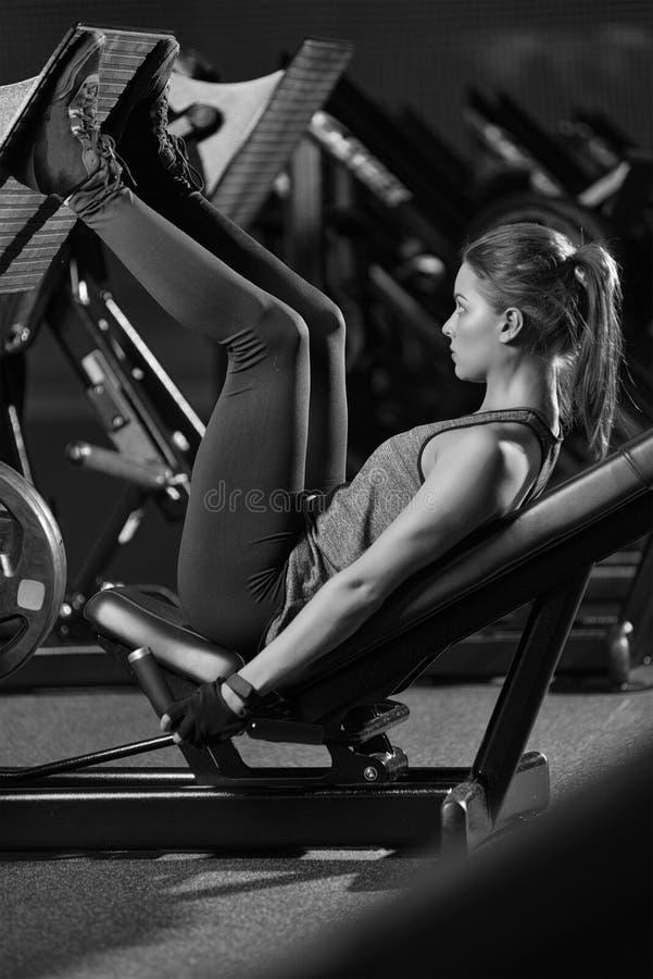 La donna allegra che usando i pesi preme la macchina per le gambe Ginnastica immagini stock libere da diritti