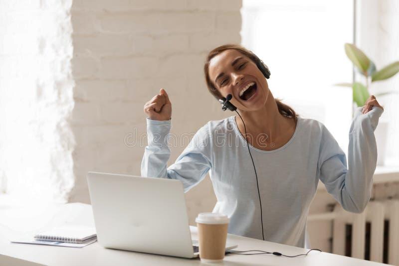 La donna allegra in cuffie con il microfono facendo uso del computer portatile, canta fotografia stock