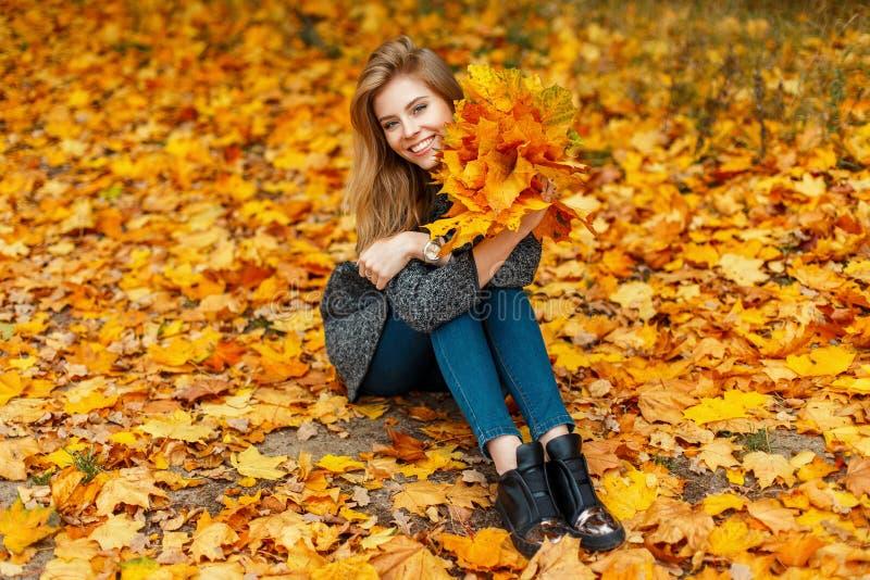 La donna allegra divertente in un cappotto tiene un mazzo di giallo di autunno fotografie stock libere da diritti