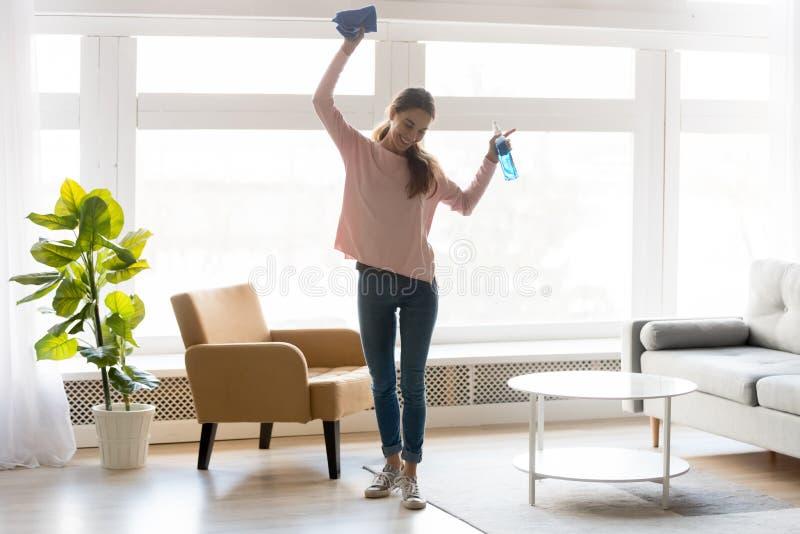 La donna allegra fa la casa che pulisce tenendo il detersivo della bottiglia dello spruzzo dello straccio immagine stock libera da diritti