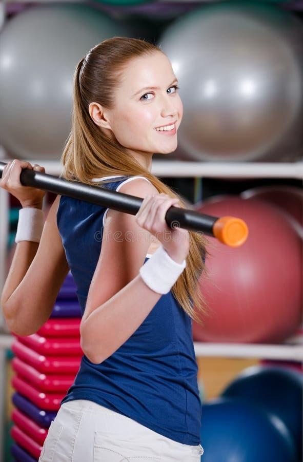 La donna allegra risolve con il bastone relativo alla ginnastica immagini stock