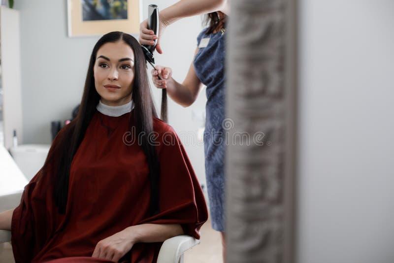 La donna allegra sta avendo taglio dei capelli in salone immagini stock libere da diritti