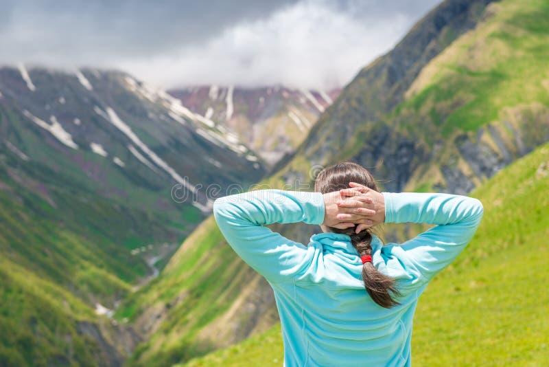 La donna ammira il bello paesaggio nelle montagne immagine stock libera da diritti