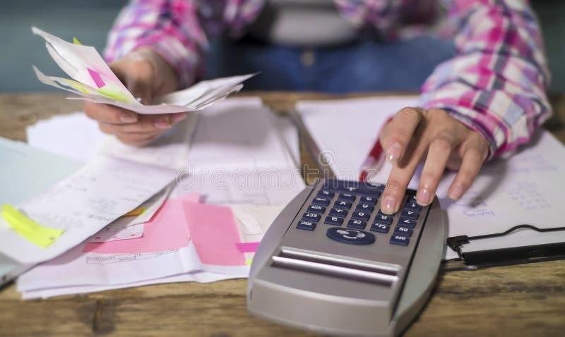 La donna anonima anonima passa il lavoro con le fatture di lavoro di ufficio della banca ed i documenti finanziari che calcolano  immagini stock