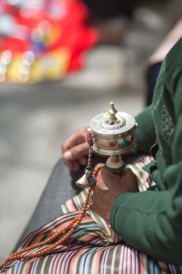 La donna anziana che prega con la preghiera arriva a fiumi Lhasa immagine stock