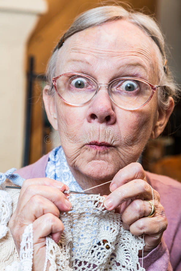 La donna anziana divertente con lavora all'uncinetto fotografie stock