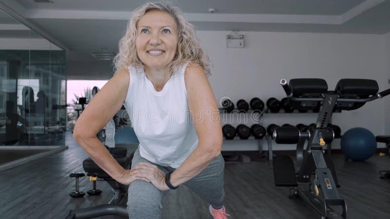 La donna anziana fa gli squattings nella palestra La donna senior della donna anziana fa gli esercizi di uno sport nella palestra immagine stock
