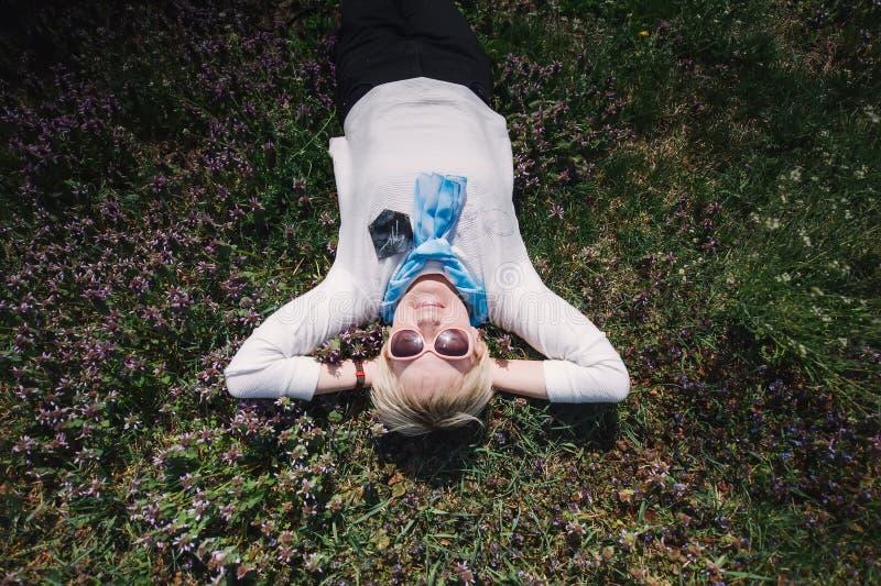 La donna anziana felice che indossa gli occhiali da sole mette sull'erba Vista superiore immagini stock libere da diritti