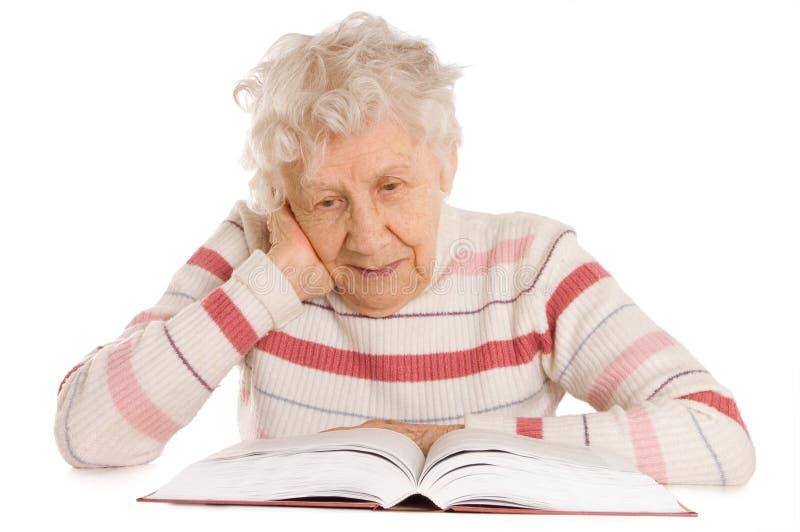 La donna anziana legge il libro immagine stock