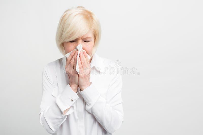 La donna anziana malata sta starnutendo in fazzoletto Sembra come ha preso un certo freddo Deve avere certo trattamento da miglio fotografie stock
