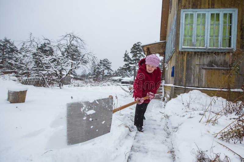 La donna anziana pulisce la neve vicino alla sua casa fotografia stock
