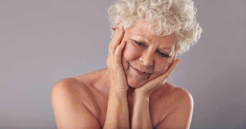 La donna anziana riporta le memorie di giovane età fotografie stock