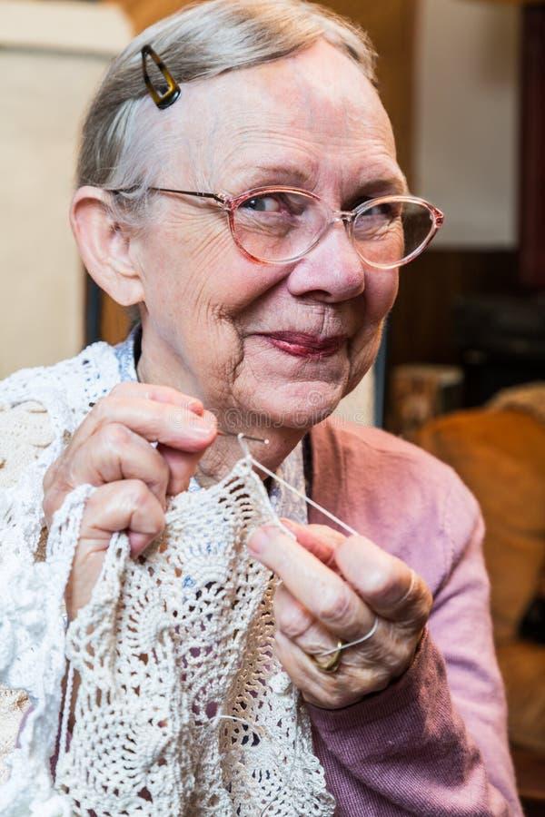 La donna anziana sorridente con lavora all'uncinetto fotografie stock libere da diritti