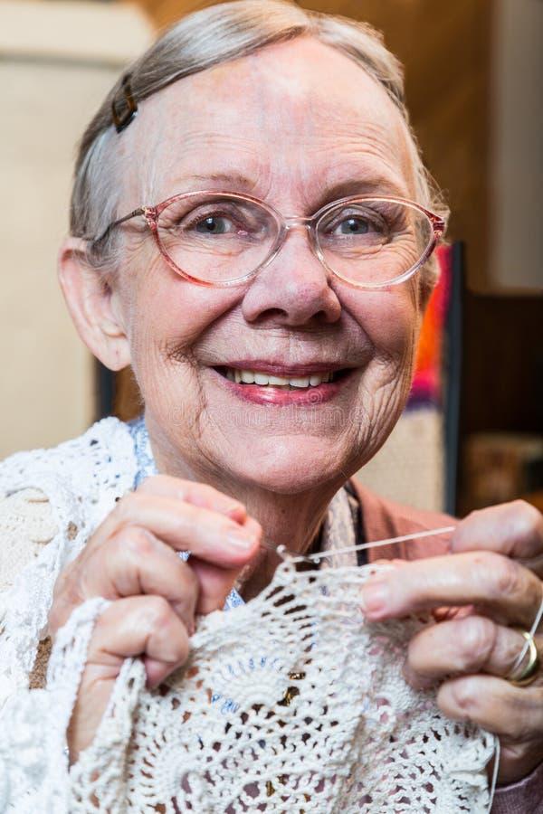 La donna anziana sorridente con lavora all'uncinetto immagini stock libere da diritti