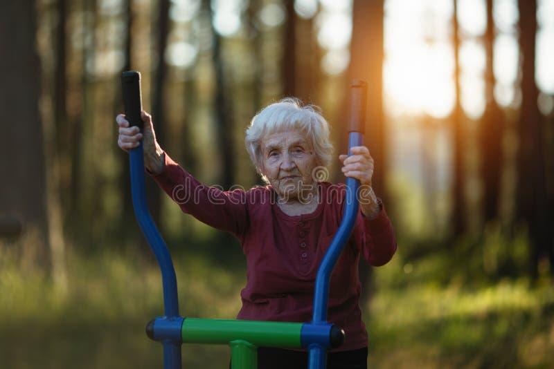 La donna anziana sta facendo gli esercizi sul campo da giuoco nel parco sport fotografia stock libera da diritti