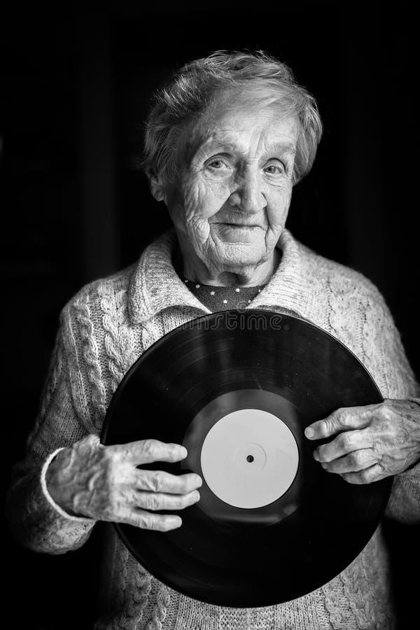 La donna anziana sta tenendo un'annotazione di vinile fotografie stock