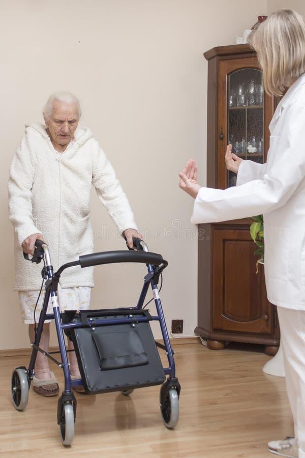 La donna anziana in una vestaglia bianca impara camminare con un balcone con l'assistenza di un infermiere fotografie stock