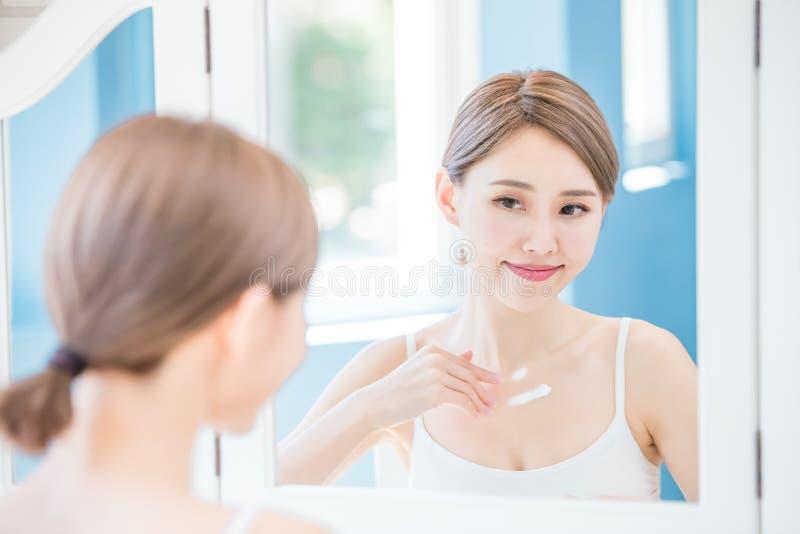 La donna applica la crema con il collo immagini stock