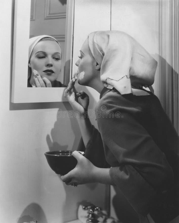 La donna applica la maschera di protezione fotografie stock