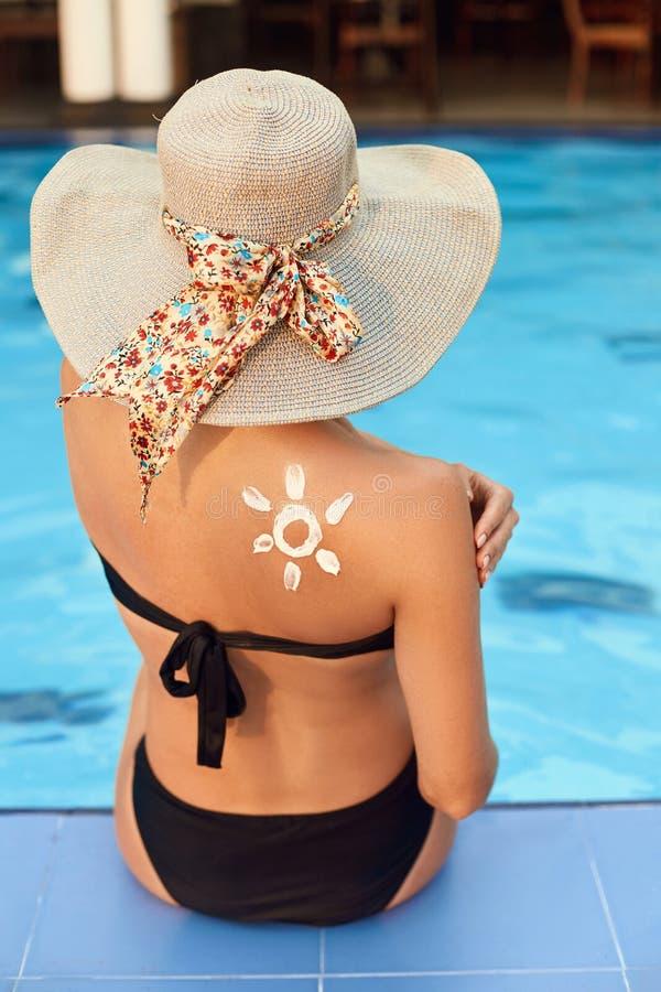 La donna applica la protezione della crema del sole sulla spalla abbronzata Cura del corpo di protezione di invecchiamento del so immagini stock libere da diritti